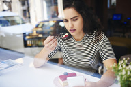 Young woman using cell phone and eating cake at an cafe in the city - ABIF00686