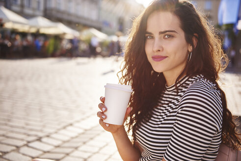 Portrait of beautiful young woman with takeaway coffee in the city - ABIF00689