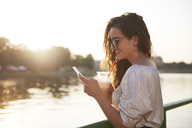 Smiling young woman with cell phone and takeaway drink at the riverside at sunset - ABIF00695