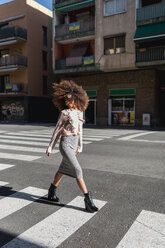 Young woman with afro hairdo crossing the street in the city - MAUF01489