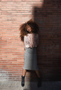 Portrait of beautiful young woman with afro hairdo at brick wall in sunshine - MAUF01492