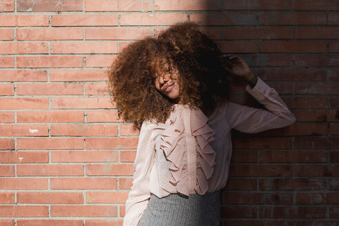 Portrait of beautiful young woman with afro hairdo at brick wall in sunshine - MAUF01495