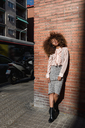Young woman with afro hairdo standing at brick wall in the city - MAUF01498