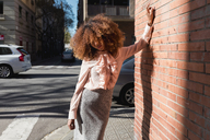 Portrait of beautiful young woman with afro hairdo leaning against brick wall in the city - MAUF01501