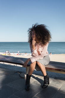Beautiful young woman with afro hairdo sitting on a bench at the beach - MAUF01504