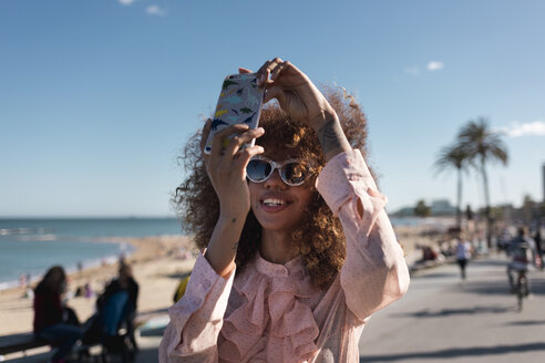 Smiling stylish young woman taking a selfie at seaside promenade - MAUF01507