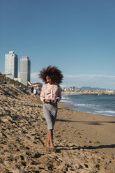 Young woman with afro hairdo walking on the beach - MAUF01513