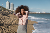 Portrait of beautiful young woman with afro hairdo standing on the beach - MAUF01516