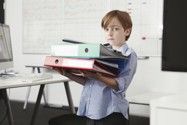 Boy holding pile of ring binders - CUF42985