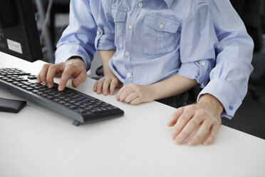 Boy sitting on father's lap using computer keyboard - CUF42994