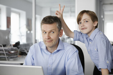 Father using laptop, son making peace sign behind his head - CUF42997