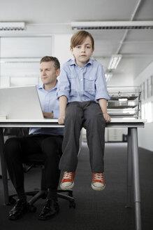 Boy sitting on desk with businessman working - CUF43000