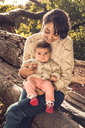 Mother and baby sitting on log - CUF43135