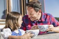 Close up portrait of father and daughter outside chalet, Tyrol, Austria - CUF43156