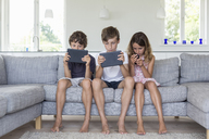 Brothers and sister on sofa with digital tablets and mobile - CUF43195