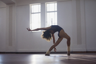 Graceful, flexibility young female dancer practicing in dance studio - HOXF03624