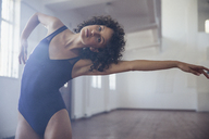 Graceful young female dancer practicing in dance studio - HOXF03630