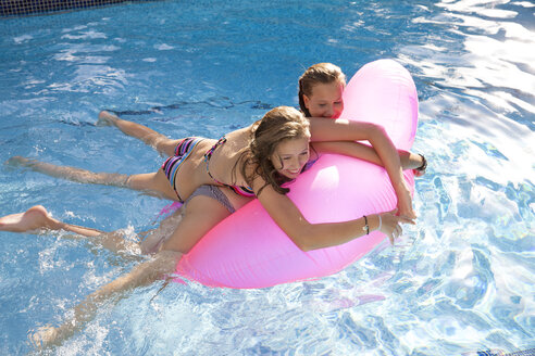 Two teenage girls holding onto air bed in swimming pool - CUF43358
