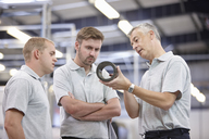 Manager discussing component in engineering factory - CUF43394