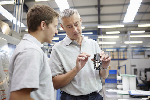 Manager and working looking at component in engineering factory - CUF43397