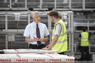 Warehouse worker and manager discussing order in engineering warehouse - CUF43415