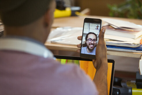 Businessman video chatting with colleague on smart phone - CAIF20963