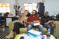 Happy creative business people taking selfie in casual open plan office - CAIF21002
