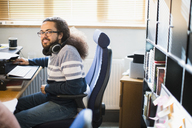 Portrait smiling, confident creative businessman with headphones working in office - CAIF21008