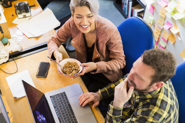 Creative business people eating cereal, working at laptop on office - CAIF21065