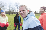 Portrait smiling, confident man boxing with friends in park - CAIF21119