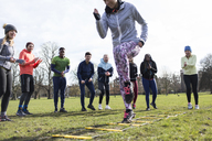 Team cheering woman doing speed ladder drill in sunny park - CAIF21122