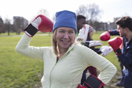 Portrait smiling, confident senior woman boxing in park - CAIF21125