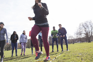 Team cheering woman doing speed ladder drill in sunny park - CAIF21128