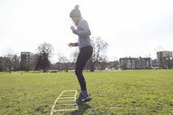 Woman practicing speed ladder drill in sunny park - CAIF21131