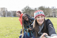 Determined team pulling rope in tug-of-war in park - CAIF21140