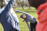 Woman exercising, stretching in park - CAIF21149