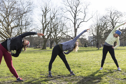 Women runners stretching in sunny park - CAIF21155