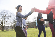 Enthusiastic woman high-fiving classmate, exercising in sunny park - CAIF21161