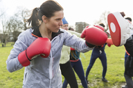 Determined, tough woman boxing in park - CAIF21173