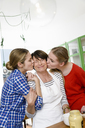 Portrait of two daughters kissing mother on cheek - CUF43544
