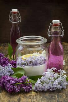 Glass bottles of homemade lilac sirup and ingredients in glass - LVF07302