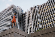 Beautiful woman wearing dungarees, standing on ledge in front of modern high-rise building - KKAF01219