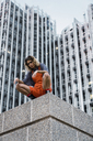 Beautiful woman wearing dungarees, crouching on ledge in front of modern high-rise building - KKAF01222