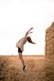 Happy young woman jumping in field - ACPF00120