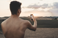 Shirtless young man taking smartphone selfie - ACPF00141
