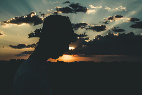 Silhouette of a young man with hat at sunset - ACPF00144