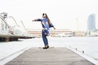 Spain, Barcelona, happy young woman with headphones dancing on jetty - JNDF00005