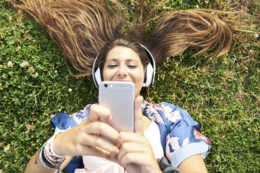 Portrait of smiling woman lying on a meadow listening music with headphones and smartphone - JNDF00008