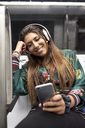 Portrait of smiling woman with  headphones looking at cell phone in underground train - JNDF00014