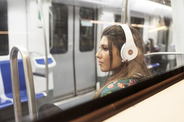 Portrait of young woman listening music with headphones in underground train - JNDF00017